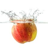 Nice apple falling into water. Ripe apple falling into water, splashes all around Royalty Free Stock Image