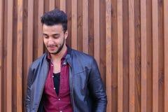 Nice-att se den arabiska unga mannen står den near väggen och leenden, Laug Arkivbilder