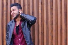 Nice-att se den arabiska unga mannen står den near väggen och leenden, Laug Arkivfoto