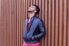 Nice-att se den arabiska unga mannen står den near väggen och leenden, Laug Arkivfoton