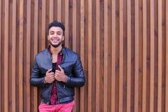 Nice-att se den arabiska unga mannen står den near väggen och leenden, Laug Royaltyfri Bild