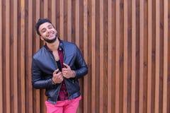 Nice-att se den arabiska unga mannen står den near väggen och leenden, Laug Royaltyfria Foton