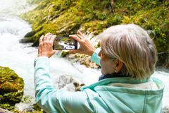 Nice attractive elderly mature woman with shiny grey hair taking photos and selfies outdoor stock images