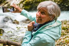 Nice attractive elderly mature woman with shiny grey hair taking photos and selfies outdoor royalty free stock image