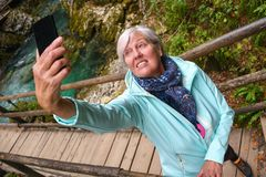 Nice attractive elderly mature woman with shiny grey hair taking photos and selfies outdoor royalty free stock photos