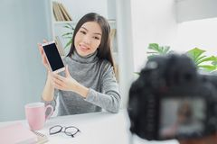 Nice and attractive girl is showing her new phone to the camera. She is recording new vlog for her channel. Girl wants royalty free stock photo