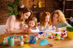 Nice attractive lovely cheerful ladies helping assisting girls doing decorative materials festive preparation in house royalty free stock image