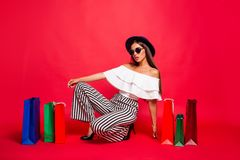 Nice attractive trendy stylish elegant lady wearing eyeglasses e. Yewear off-the-shoulders ruffles blouse top high heels shoes sitting among colorful bags royalty free stock photos