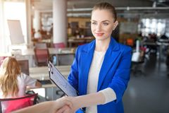 Nice and attractive woman is shaking hand. Also she is holding some papers in her right hand. Woman looks calm and royalty free stock photo