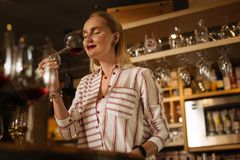 Nice attractive woman standing with a wine glass. Delicious drink. Nice attractive woman standing with a wine glass while working as a sommelier stock photos