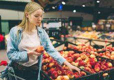 Nice and attractive youn woman is taking some apples at the store. She is choosing the best one. Royalty Free Stock Images