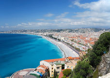 Nice between azure sea and blue sky. Azure sea bay and blue sky of mediterranean coast, white clouds above old and modern district of city Nice, mountains in the royalty free stock image