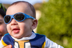 Nice baby with blue googles. Cute 6 months old baby with Light brown hair in white, blue and brownish long-sleeved shirt wearing blue googles is embraced and Royalty Free Stock Images