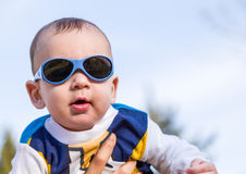 Nice baby with blue googles. Cute 6 months old baby with Light brown hair in white, blue and brownish long-sleeved shirt wearing blue googles is embraced and Royalty Free Stock Photography