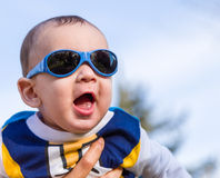 Nice baby with blue googles. Cute 6 months old baby with Light brown hair in white, blue and brownish long-sleeved shirt wearing blue googles is embraced and Stock Images