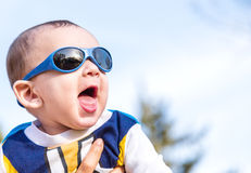 Nice baby with blue googles. Cute 6 months old baby with Light brown hair in white, blue and brownish long-sleeved shirt wearing blue googles is embraced and Royalty Free Stock Image