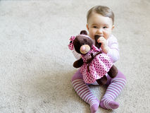 Nice baby girl bites the paw of the toy bear Royalty Free Stock Photography