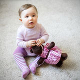 Nice baby girl sitting on the floor with toy bear Royalty Free Stock Photos