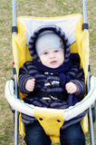 Nice baby outdoors on yellow buggy in spring Stock Images