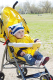 Nice baby outdoors on yellow buggy in spring Royalty Free Stock Photos