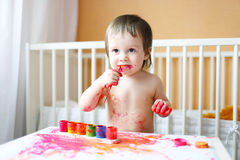 Nice baby with paints Royalty Free Stock Photos