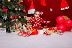 A nice baby in pajamas was delighted with a lot of Christmas pre. Sents near the Christmas tree Royalty Free Stock Photo