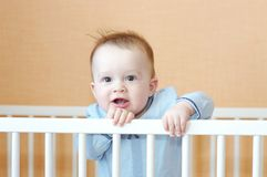 Nice baby in white bed. Nice baby age of 8 months in white bed Royalty Free Stock Images