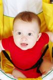 Nice baby in a yellow baby carriage. Nice baby age of 7 months in a yellow baby carriage royalty free stock photo
