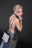 Nice Backside. Mature Lady with evening dress and handbag Stock Photo