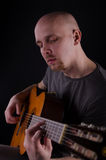 Nice bald guy with a guitar. In studio Royalty Free Stock Photos
