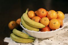 A nice basket of fruit bananas and oranges on a wooden table stock photo