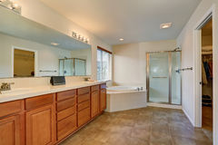 Nice bathroom with lots of space. Modern brown cabinets, double sink and corner white bath tub Stock Photo