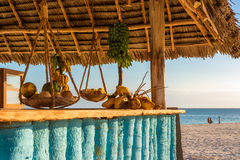 Nice beach bar zanzibar. In the picture beach bar in Nungwi ( Zanzibar ) at sunset , with exposed coconut , banana and tropical fruit .This bar is made with cane Royalty Free Stock Images