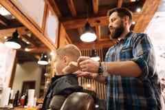 Nice bearded hairdresser doing his job Stock Photography