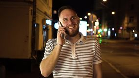 Nice bearded man have a mobile phone call. He answers it and start to chatting with somebody. Stay on night street in. Striped t shirt stock video footage