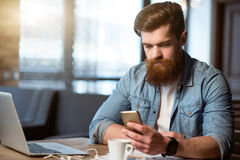 Nice bearded man sitting at the table stock photography