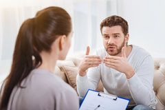 Nice bearded man talking to the psychologist. Personal problems. Nice bearded cheerless men gesticulating and trying to explain his problem while talking to the royalty free stock photos