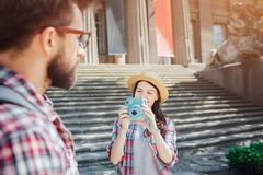 Nice and beautfiul young female tourist stand at steps and hold blue camera. She takes picture of her boyfriend and look stock images