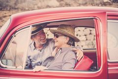 Nice beautiful couple of senior adult people inside an old red vintage car enjoy and stay together in outdoor travel leisure