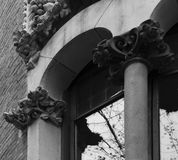 Nice and beautiful floral details by the window. Shot in black and white, detail on the sculpture on the facade of this historic building representing some Royalty Free Stock Photo