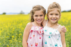 Beautiful girls in a field of yellow flowers Royalty Free Stock Photo