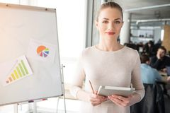Nice and beautiful picture of cheerful woman standing near flipchart. Sh hold a notebook and a pen. Girl did some. Preparation for meeting stock images