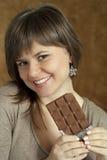 Nice beautiful woman holding a chocolate bar Stock Photos