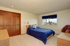 Nice bedroom in creamy tones with small bed, built in wardrobe Stock Images