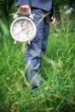 Nice big alarm clock in his hand men. In nature stock images