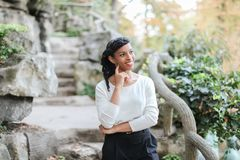 Nice black female person standing near rock and stone stairs in park, having ponytail. Nice black female person standing near rock and stone stairs in park Royalty Free Stock Photos