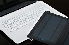 Nice black portable solar charger lying on top of white laptop, modern business technology concept, studio background Royalty Free Stock Image