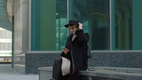 Nice blond girl in black coat and hat listens to music with smartphone headphones against city street slow motion stock footage
