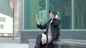 Nice blond girl in black coat and hat with smartphone headphones against city street slow motion stock footage