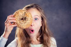 Blond girl looking through a big bagel. Nice blond girl in front of gray background looking through a big bagel royalty free stock images